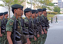 A row of young soldiers wearing green camouflage uniforms and dark green berets and holding rifles, standing at attention.