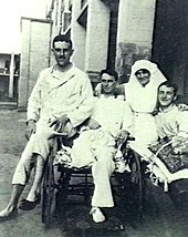 Three men in hospital pyjamas sitting with female nurse