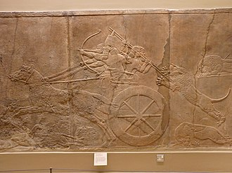 Lion Hunt of Ashurbanipal - The king shoots arrows from his chariot, while huntsmen fend off a lion behind