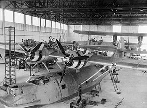 No. 205 Squadron RAF - Consolidated Catalina Mark Is of No. 205 Squadron RAF undergoing servicing in their hangar at RAF Seletar, Singapore. One of the Squadron's Short Singapore Mark IIIs biplane flying boats can be seen in the right background.