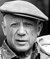 An elderly Pablo Picasso in a cloth cap, grinning at the camera