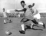 Photograph of a man dribbling a ball past an opponent