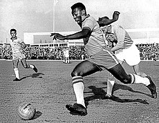 A dark-skinned young man in soccer attire is pictured in mid-stride as he sprints with the ball past an opposing player, who looks tired and has given up attempting to chase him.