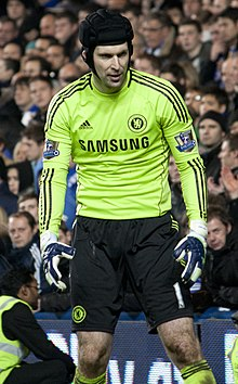 Petr Cech wearing a rugby style headgear, a volt-green long-sleeved goalkeeper's shirt with the Chelsea FC, Adidas and Samsung logos printed on the front and Premier League champions patches on the sleeves, goalkeeper gloves, black shorts with a number 1 on the left-leg side and Chelsea logo on the right-leg side, and volt-green socks.