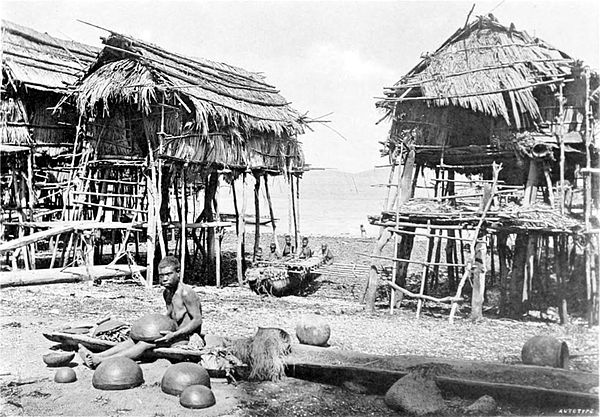 Black and white photograph of a woman making pots on a beach, with three huts-on-stilts in the background.