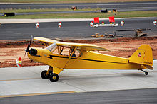 "A bright yellow, single-propeller light airplane is sitting on a paved surface at what appears to be an airport. A man is sitting in the pilot's seat, and the propeller is turning. On the tail of the plane is a logo consisting of a small bear holding a sign that says, ""Cub"". The number on the tail rudder is N70843."