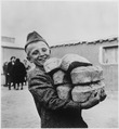 Polish youngster with his arms loaded down with bread made from flour supplied by the American Red Cross. Smile is in... - NARA - 531156.tif