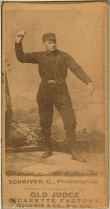 A sepia-toned blurry image of a man wearing an old-style dark-colored baseball uniform