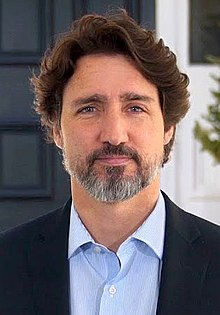 Portrait photograph of Trudeau smiling in front of Rideau Cottage.