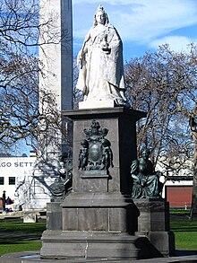 Grande figura de uma mulher usando uma coroa e túnicas, posicionada em um pedestal alto