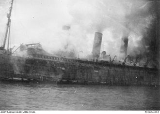 RMS Empress of Asia - The starboard-side view of the burning vessel, showing extensive damage from the Japanese aerial-attack on the ship.