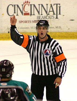 Referee - An ice hockey referee, wearing vertical black and white stripes
