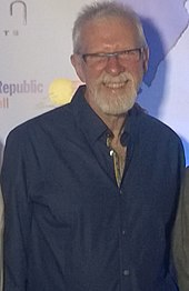 Man with glasses and a blue shirt is staring at the camera.