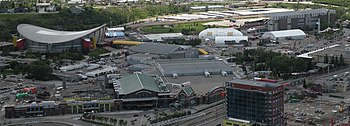 A downward-looking image of numerous buildings. A large arena is situated to the left, behind a building with a green peaked roof. To the right in the distance is a dirt race track.