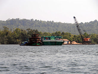 Land reclamation in Singapore - A sand mining boat dredges Cambodia's Tatai River.