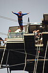 An individual dressed as Superman bungee jumping