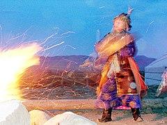 Schamanin w%C3%A4hrend einer Kamlanie-Zeremonie am Feuer in Kysyl