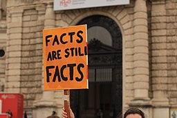 [Foto: Person hält ein orangenes Schild hoch, auf dem steht: Facts are still facts (Fakten sind immer noch Fakten)]