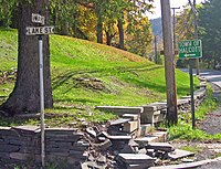 "A street corner with the lower portions of a telephone pole and a tree visible above a small stone retaining wall that has crumbled in the center of the photo. On the left is a black and white street sign with ""Main Street"" on top and ""Lake Street"" on bottom. At the right a white on green sign has the words ""Town of Halcott"" and an arrow pointing to the left"