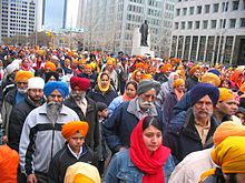 Large group of Sikh men and women on a city street