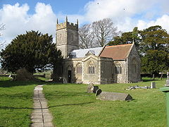 Stone building with square tower. Foreground is grass with gravestones.