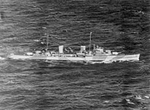 Black-and-white aerial photograph of a two-funnelled cruiser underway. Alternating light and dark bands are painted on the side of the ship.
