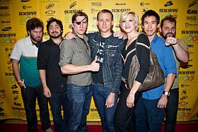 Seven of the filmmakers posing for a photo on the red carpet.
