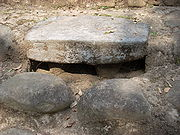 A thick, flat stone set into a wide step, it has a dark hollow underneath with two short stone legs supporting the altar. Two large, smoothly rounded cobbles are set into the step below the altar.
