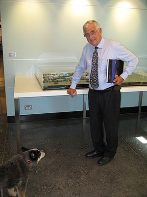 "Terry Snow - Terry Snow and his Blue Heeler, Chilli. Snow is holding the book ""Canberra Airport: A Pictorial History"" (2009) by his wife, Ginette Snow. He is standing beside the model of Brindabella Business Park."
