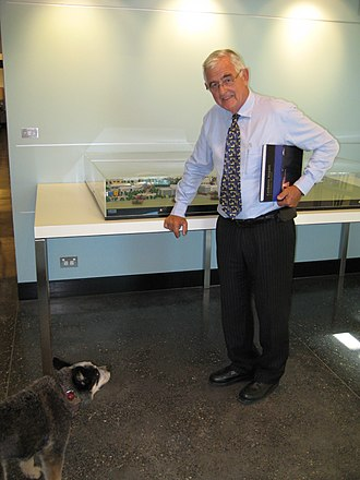 """Terry Snow - Terry Snow and his Blue Heeler, Chilli. Snow is holding the book """"Canberra Airport: A Pictorial History"""" (2009) by his wife, Ginette Snow. He is standing beside the model of Brindabella Business Park."""