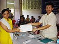 """The Panchayat Raj & Rural Development Minister of Assam Shri. Chandan Brahma giving away first prize to Miss Deepa Kalita in All Assam Essay Competition on the topic """"Guwahati - City of my dream"""" at the valedictory function.jpg"""