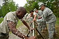U.S. Army Sgt. Chavis Avery, left, with Headquarters and Headquarters Company, 105th Military Police Battalion, North Carolina Army National Guard, rinses himself with water after being exposed to oleoresin 130501-Z-AY498-006.jpg