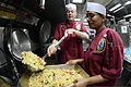 U.S. Navy Culinary Specialists 2nd Class Donald Liggett, left, and Rupa Raass, both assigned to the guided missile destroyer USS McCampbell (DDG 85), prepare lunch for the ship's crew members March 4, 2013 130304-N-TG831-108.jpg