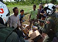 US Navy 050113-N-8629M-098 Aviation Machinist's Mate 2nd Class Derek Barnum talks with an appreciative Indonesian men after dropping a load of humanitarian relief supplies for tsunami victims near the coastal regions of Indones.jpg