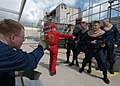 US Navy 050323-N-8977L-012 Lead instructor for basic flight deck firefighting, Aviation Boatswain's Mate 1st Class Jason Pick, center, shows students how to relieve a nozzle man at Fleet Training Center (FTC), San Diego.jpg