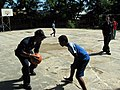 US Navy 071211-N-0000J-001 Operations Specialist 2nd Class Azariah Lindsey, assigned to the guided-missile cruiser USS Port Royal (CV 73), takes a break from painting a local schoolhouse to go one-on-one on the basketball court.jpg