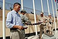 US Navy 080704-F-7045D-001 Retired Navy Cmdr. Joseph Agra III, left, the Afghan National Army Air Corps logistics mentor, reads a citation regarding an American flag with 48 stars that was raised during a ceremony July 4 at Cam.jpg