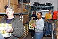 US Navy 091123-N-1580K-944 Chief Builder Dan Meddison, Logistics Specialist 2nd Class Gloria Pearson and Sailors carry boxes of canned vegetables while at the Mid Coast Hunger Prevention Program (MCHPP) storehouse.jpg