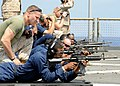 US Navy 100321-N-1082Z-133 Lance Cpl. Benjamin Stroope watches Hospital Corpsman Seaman Richard L. Williams during weapons qualification.jpg