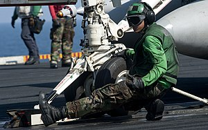 US Navy 120104-N-OY799-114 Aviation Boatswain's Mate (Equipment) 3rd Class Carlaldrin Milana signals for a fixed wing aircraft to move forward on t.jpg