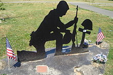A metal cutout 2-D sculpture of a soldier kneeling at the grave of a fallen comrade.