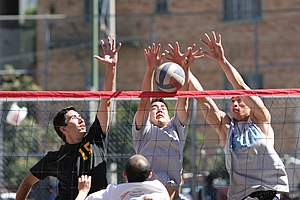Volleyball variations - A triple block in a game of nine-man volleyball