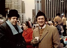 Two men in winter coats and hats standing in crowd in front of tall city buildings
