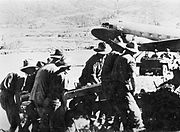 A group of men in slouch hats struggle with a large object. In the background is a jeep and a Dakota.