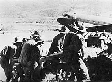 Soldiers in slouch hats manhandle an artillery piece from a plane