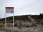 """Area 51 border and warning sign stating that """"photography is prohibited"""" and that """"use of deadly force is authorized"""" under the terms of the 1950 McCarran Internal Security Act. A government vehicle is parked on the hilltop; from there, security agents observe the approach to Groom Lake."""