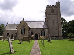 Stone church with square tower. In the foreground are a path and gravestones