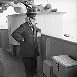 Winston Churchill wearing leather ear defenders watches gunnery practice on board HMS RENOWN whilst he was returning from Canada, September 1943. H32941.jpg