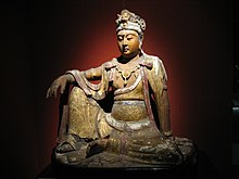 A wooden carving of a female human figure, sitting with one knee on the ground and one knee pointing up, with a hand resting on that knee. The carving includes loose fitting clothing, which is covered mainly in gold foil.
