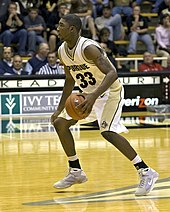 an African American basketball player in a Purdue #33 jersey is dribbling a basketball